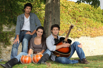 Men and young woman with music instruments outdoors
