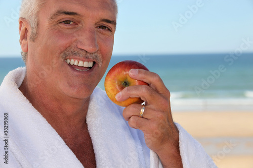 Senior man in bathrobe eating an apple