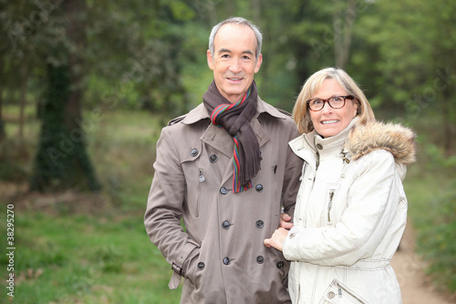 Elderly couple walking through woods