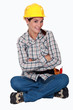 A cute female construction worker sitting on the floor.