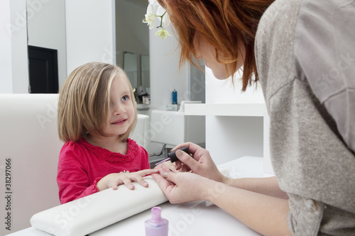 Woman applying nail polish on little girl's hand