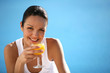 Brunette drinking fruit juice by swimming pool