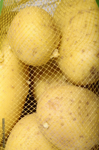 Some yellow potatoes sold in a yellow net