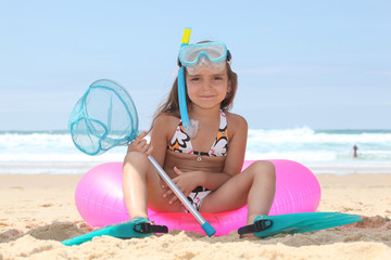 little girl at beach with sitting on buoy with diving equipment
