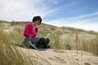 Woman using her laptop in a sand dune
