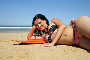 Brunette laying seductively on surfboard