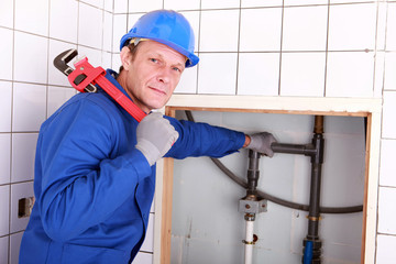Experienced plumber using a large wrench in a bathroom