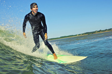 Young surfer smiles surfing wave in wetsuit sunny day