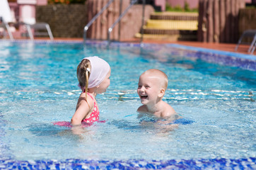 Smiling boy and little girl swimming in pool