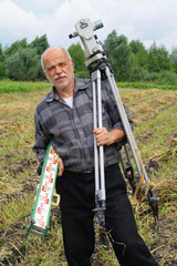 An elderly man with a theodolite