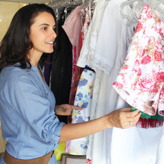 Schöne Frau schaut sich Blusen im Laden an