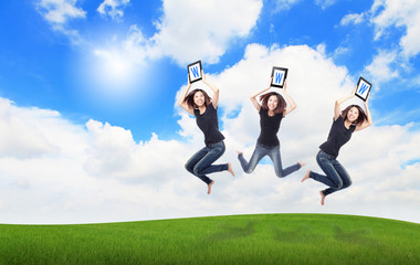 Happy Girl Jump and show touch pad computer on the meadow