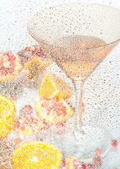 Martini and fruits through the water glass