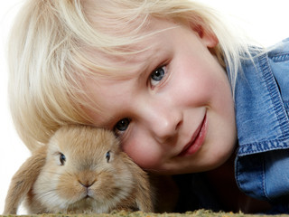 Little girl is huddling up to her cute bunny