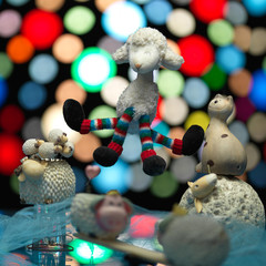 group sheep toys playing, colorful lights background