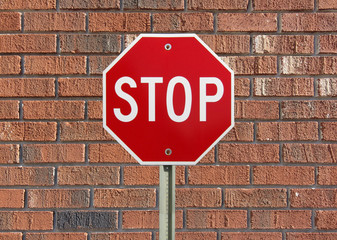 Stop sign against brick wall