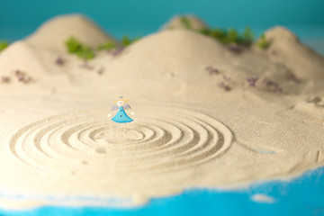 little toy angel in miniature landscape