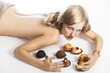 blond sexy girl eating pastry, her arms are around the pastries