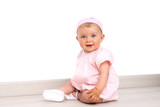 Baby girl with blue eyes sitting on the floor