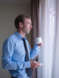 Businessman drinking coffee and looking out of window