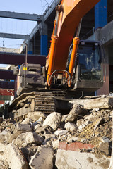 A digger sits on waste from a demolition site in Tours