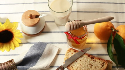 A healthy breakfast with milk, honey, bread and fruit