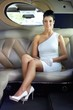 Happy woman sitting in limousine