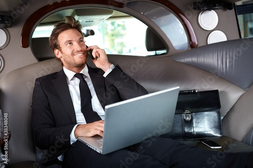 Smiling businessman in luxury car working