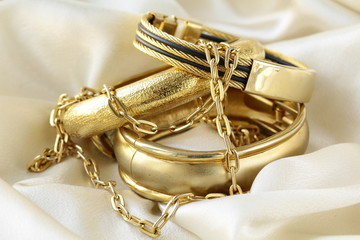 gold jewelry, bracelets and chains on silk