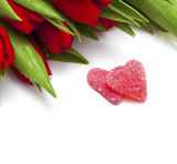 red tulips and two heart-shaped candies