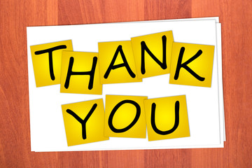 Word THANK YOU on stickers on table