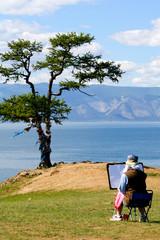 Женщина художник рисует на берегу озера Байкал