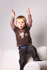 kleinkind steht überrascht auf der couch