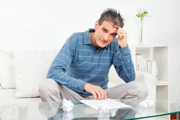 Mann mit zerknüllten Papierkugeln am Tisch