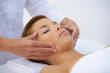 Woman laying on back have face massaged
