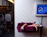 Small two year old baby girl sleep in a bassinet on a airplane