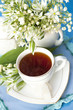 tea in a cup of white flowers and lilies of the valley