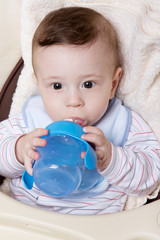 Adorable little baby boy with feeder