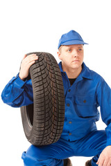 Mechanic is holding one car tire on white background