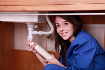 Young woman fitting the waste pipe on a kitchen sink