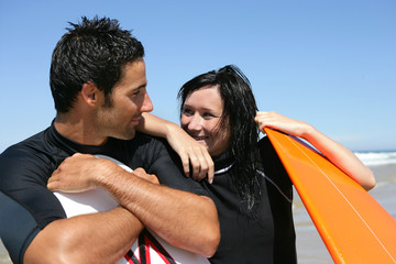 Couple stood at the beach in wet-suits waiting to surf