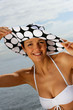 Woman wearing hat and bikini at the beach