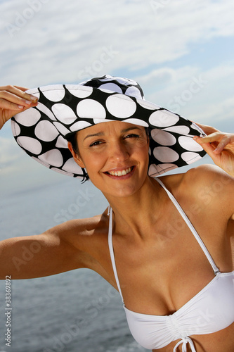 Woman wearing hat and bikini at the beach