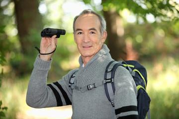 Grey haired man with binoculars