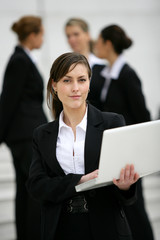 Businesswoman stood outdoors with colleagues in the background