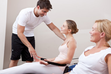 Women exercising with instructor help