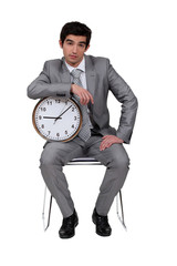 Businessman sat with clock
