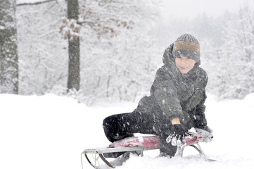 Boy on sled in winter forest