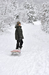 boy walking with sleds