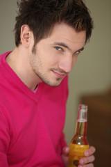 Dark-haired man holding bottle of beer